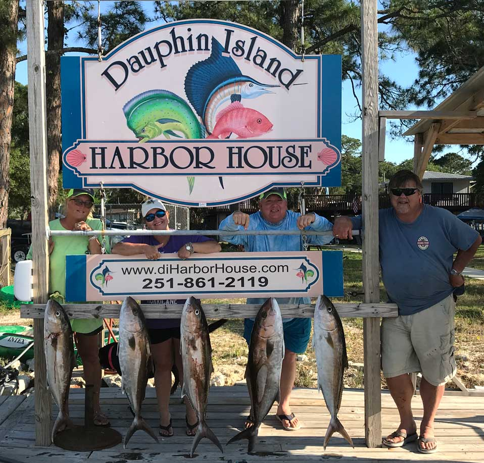 Dauphin Island Harbor House sign with group and their caught fish