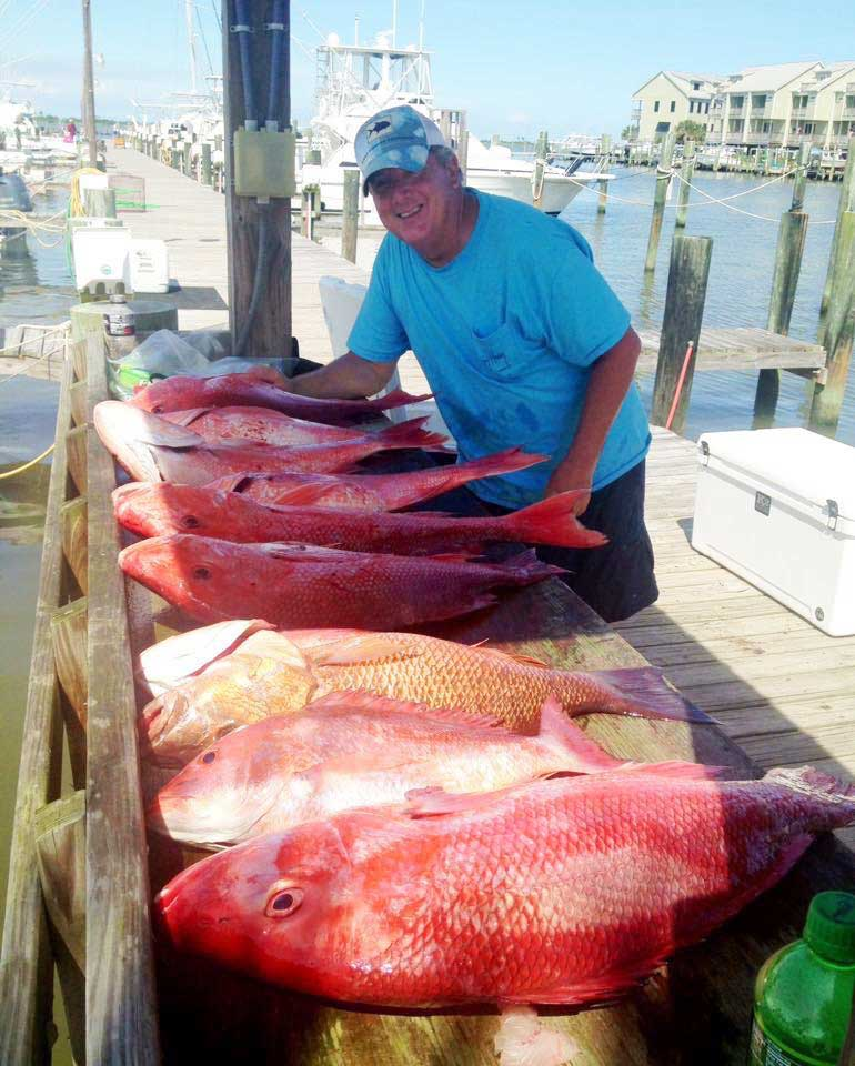 Man with a bunch of caught large redfish